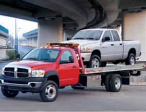 a picture for a towing truck carrying a pickup car under a bridge